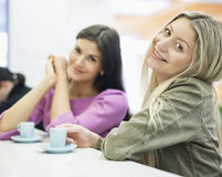 Porträt von den jungen Geschäftsfrauen, die am Cafeteriatisch lächeln lizenzfreie stockbilder