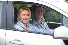 Porträt von den jungen Paaren, die aus Auto-Fenster heraus schauen Lizenzfreies Stockbild