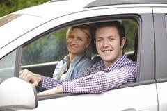 Porträt von den jungen Paaren, die aus Auto-Fenster heraus schauen Stockbilder