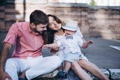 Porträt von den jungen stilvollen Paaren, die auf der Pflasterung in altem sitzen, besitzen Hübscher Junge glücklich Stockbild