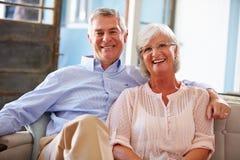 Porträt von den lächelnden älteren Paaren, die auf Sofa At Home sitzen lizenzfreies stockfoto