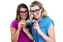 Porträt von den lächelnden Freunden, die Digitalkamera halten Lizenzfreies Stockfoto