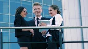 Porträt von den lächelnden Geschäftsleuten, die draußen sprechen Eins von ihnen etwas zu anderen auf ihrer Tablette zeigend stock video