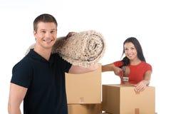 Porträt von den lächelnden Paaren, die auf neue Wohnung sich bewegen Lizenzfreies Stockfoto