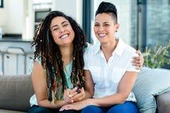Porträt von den lesbischen Paaren, die zusammen auf Sofa und dem Lächeln sitzen stockbild