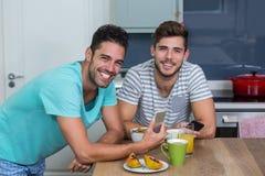 Porträt von den männlichen Freunden, die Telefon verwenden stockfotos