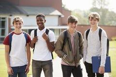 Porträt von den männlichen Jugendstudenten, die um College-Campus gehen stockfotografie