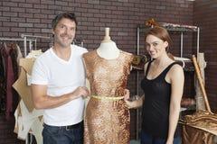 Porträt von den Modedesignern, die zusammen an einer Ausstattung im Entwurfsstudio arbeiten stockfotografie