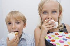Porträt von den netten Geschwister, die Geburtstagskuchenscheiben im Haus essen Lizenzfreies Stockbild