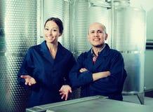Porträt von den netten zwei Mitarbeitern, die auf Weinfabrik stehen Lizenzfreie Stockbilder