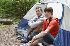Porträt von den Paaren, die durch Zelt sitzen lizenzfreie stockfotos