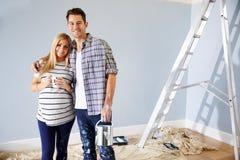 Porträt von den Paaren, die Kindertagesstätte für neues Baby verzieren stockfotografie