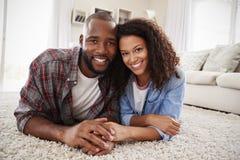 Porträt von den Paaren, die zu Hause auf Wolldecke im Aufenthaltsraum liegen lizenzfreie stockfotos