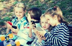 Porträt von den positiven Kindern, die mit Telefonen spielen stockfotografie