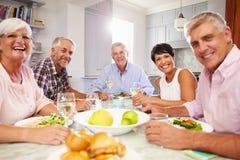 Porträt von den reifen Freunden, die zu Hause Mahlzeit zusammen genießen stockbild