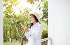Portr?t von den sch?nen asiatischen Frauen unter Verwendung des intelligenten Telefons und von L?cheln an im Freien, am Positiv d stockbild