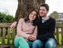 Porträt von den schönen jungen Paaren, die auf einer Bank in einem Park sitzen Lizenzfreie Stockfotografie