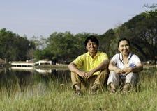 Porträt von den schönen Paaren, die auf Gras sitzen lizenzfreies stockbild