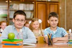 Porträt von den Schülern, die Kamera im Klassenzimmer betrachten Stockbild