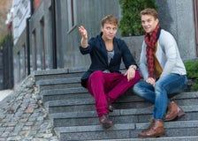 Porträt von den stilvollen modernen Zwillingsbrüdern, die auf dem sta sitzen Lizenzfreies Stockfoto