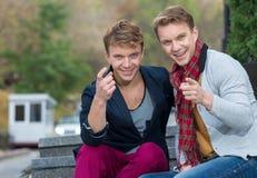 Porträt von den stilvollen modernen Zwillingsbrüdern, die auf dem sta sitzen Lizenzfreies Stockbild