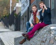 Porträt von den stilvollen modernen Zwillingsbrüdern, die auf dem sta sitzen Lizenzfreie Stockbilder