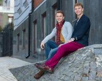 Porträt von den stilvollen modernen Zwillingsbrüdern, die auf dem sta sitzen Stockfotos