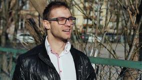 Porträt von den tragenden Augengläsern des jungen Mannes, die in die Stadtstraßen gehen stock video