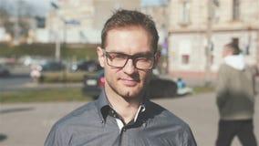 Porträt von den tragenden Augengläsern des jungen Mannes, die in die Stadtstraßen gehen stock video footage