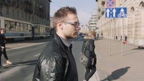 Porträt von den tragenden Augengläsern des jungen Mannes, die in die Stadtstraßen gehen stock footage