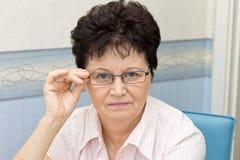 Porträt von der von mittlerem Alter tragenden Gläsern Frau zu Hause Stockbild