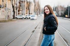 Porträt von der Rückseite des eleganten Mädchens mit dem langen Haar gehend auf Stadthintergrund Sie hat schwarze Lederjacke und  lizenzfreie stockfotografie
