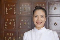 Porträt von Doktor In Front des traditioneller Chinese-Arzneischranks Stockbilder