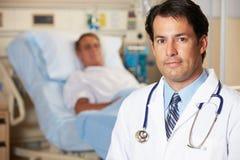 Porträt von Doktor With Patient In Background Lizenzfreie Stockfotografie
