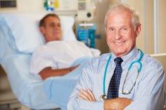 Porträt von Doktor With Patient In Background Stockfoto