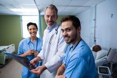 Porträt von Doktor und von Krankenschwester, die Röntgenstrahl im Bezirk überprüfen Lizenzfreie Stockfotografie