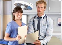 Porträt von Doktor und von Krankenschwester in Office Doktors Lizenzfreie Stockfotografie