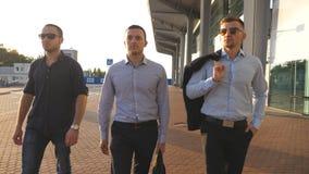Porträt von drei jungen Geschäftsmännern, die in Stadt nahe Büro gehen Geschäftsleute, die austauschen, um zusammenzuarbeiten Übe stock video footage