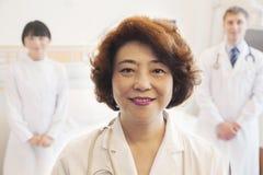 Porträt von drei lächelnden Doktoren, Ärztin an der Front lizenzfreies stockbild