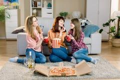 Porträt von drei netten jungen Freundinnen mit Popcornschüsseln, Pizza und Wein, sitzend auf dem Boden nahe stockbild
