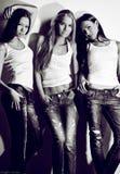 Porträt von drei schön und von den sexy Frauen, die auf weißem Hintergrund aufwerfen Stockfotografie
