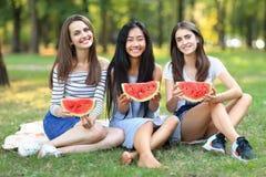 Porträt von drei schönen Mädchen mit Scheiben von Wassermelone outd lizenzfreie stockfotografie