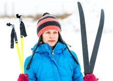 Porträt von eine junge Frau holdingskis draußen im Winter im Schneewetter lizenzfreies stockbild