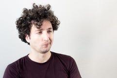 Porträt von einem jungen, kaukasisch, Brünette, gelockter behaarter Mann mit Abneigungsausdruck auf weißem Hintergrund lizenzfreie stockfotografie