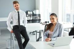 Porträt von erfolgreichen Geschäftsleuten an ihrem Arbeitsplatz Busin Lizenzfreie Stockfotos