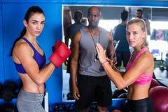 Porträt von ernsten weiblichen Boxern durch Trainer Stockbild