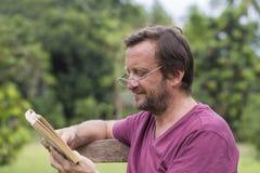 Porträt von fünfzig Jahren alten kaukasischen Mann, die ein Buch im Freien in einem Park während eines sonnigen Sommertages lesen Lizenzfreie Stockfotografie