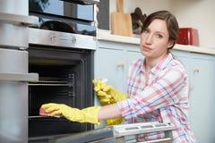 Porträt von Fed Up Woman Cleaning Oven Lizenzfreie Stockfotos