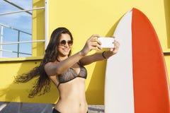 Porträt von Frauen eines herrlichen lächelnden Surfers im Bikini, der Selbstporträt mit Handykamera macht Lizenzfreie Stockfotos