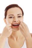 Porträt von Frauenreinigungszähnen mit Zahnseide Stockfotos